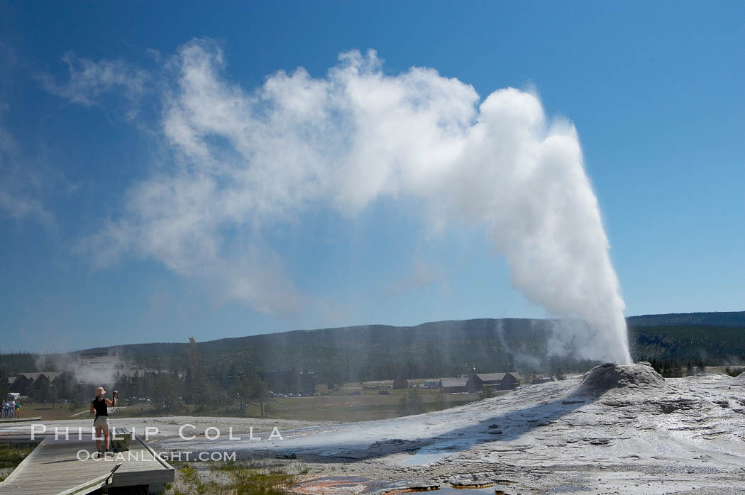 A visitor videotapes the eruption of Lion Geyser, with Old Faithful Inn visible in the distance.  Lion Geyser, whose eruption is preceded by a release of steam that sounds like a lion roaring, erupts just once or a few times each day, reaching heights of up to 90 feet.  Upper Geyser Basin. Upper Geyser Basin, Yellowstone National Park, Wyoming, USA, natural history stock photograph, photo id 13371
