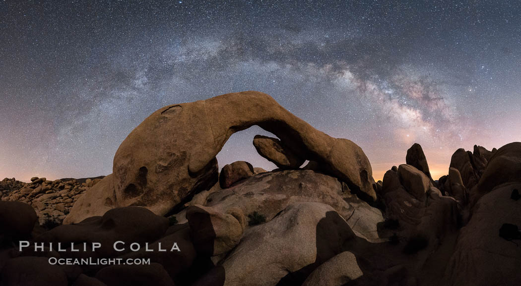 Milky Way during Full Lunar Eclipse over Arch Rock, Joshua Tree National Park, April 4 2015.  The arch and surrounding landscape are illuminated by the faint light of the fully-eclipsed blood red moon.  Light from the sun has passed obliquely through the Earth's thin atmosphere, taking on a red color, and is then reflected off the moon and reaches the Earth again to light the arch.  The intensity of this light is so faint that the Milky Way can be seen clearly at the same time