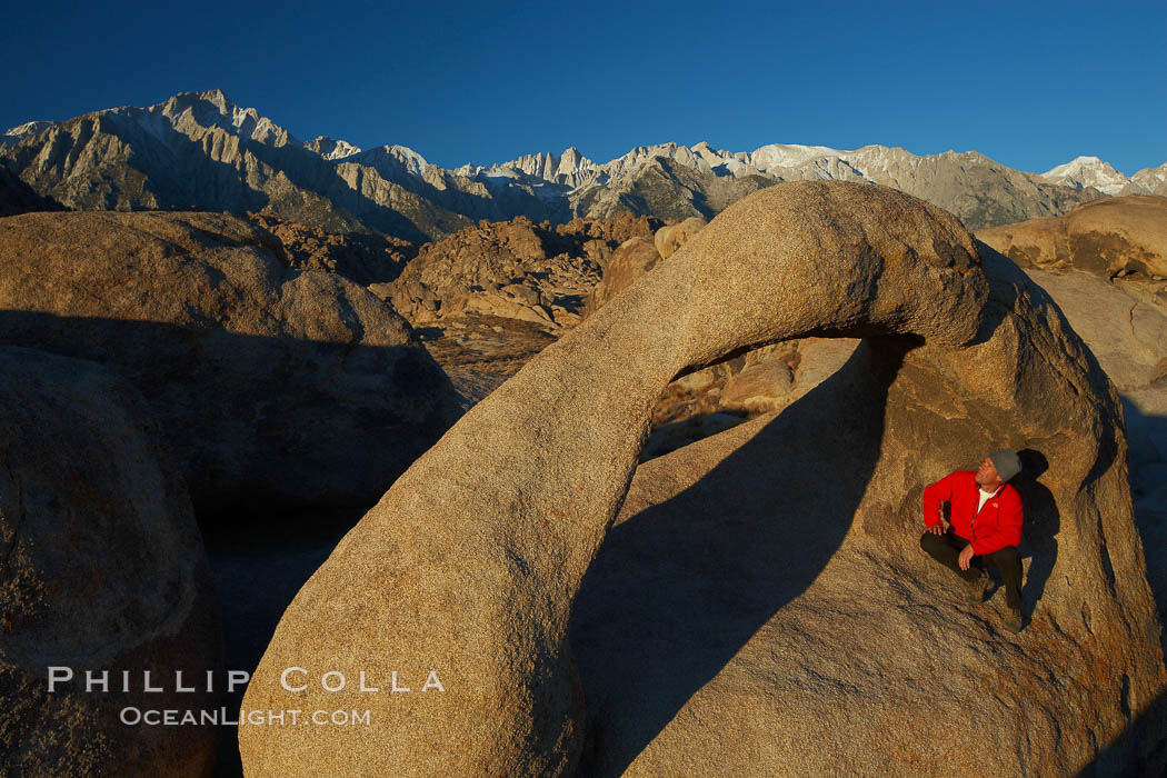 A hiker admires Mobius Arch in early morning golden sunlight, with the snow-covered Sierra Nevada Range and the Alabama Hills seen in the background. Alabama Hills Recreational Area, California, USA, natural history stock photograph, photo id 21740