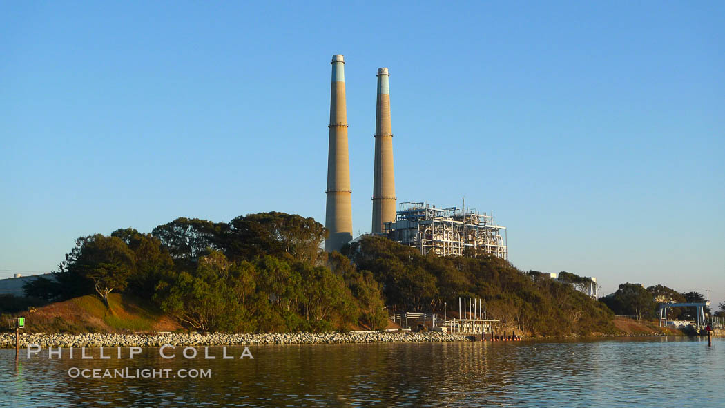 Moss Landing Power Plant rise above Moss Landing harbor and Elkhorn Slough.  The Moss Landing Power Plant is an electricity generation plant at Moss Landing, California.  The twin stacks, each 500 feet high, mark two generation units product 750 megawatts each. Moss Landing, California, USA, natural history stock photograph, photo id 21496