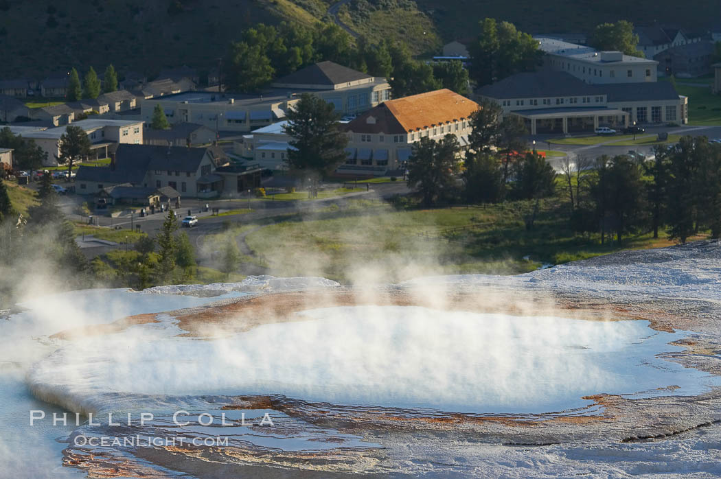 New Blue Spring steams in the cold morning air with Mammoth Hot Springs Inn in the distance. Mammoth Hot Springs, Yellowstone National Park, Wyoming, USA, natural history stock photograph, photo id 13610