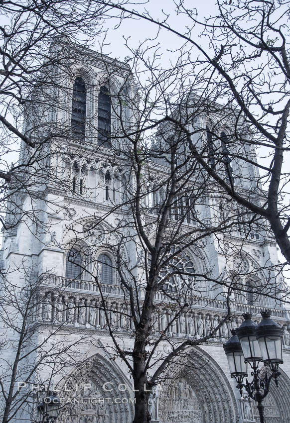 "Notre Dame Cathedral, trees and streetlamp, west facade, Paris. Notre Dame de Paris (""Our Lady of Paris""), also known as Notre Dame Cathedral or simply Notre Dame, is a historic Roman Catholic Marian cathedral on the eastern half of the Ile de la Cite in the fourth arrondissement of Paris, France. Widely considered one of the finest examples of French Gothic architecture and among the largest and most well-known churches in the world ever built, Notre Dame is the cathedral of the Catholic Archdiocese of Paris"