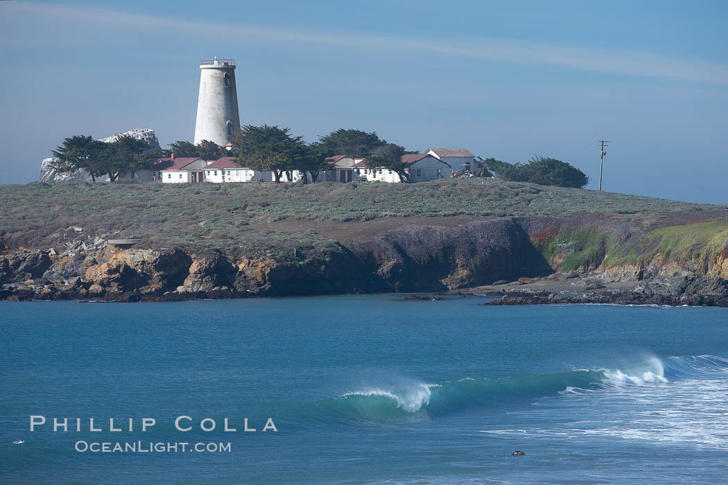 Piedras Blancas lighthouse.  Completed in 1875, the 115-foot-tall Piedras Blancas lighthouse is one of the few tall-style lighthouses on the West Coast of the United States.  Piedras Blancas, named for a group of three white rocks just offshore, is north of San Simeon, California very close to Hearst Castle.,  Copyright Phillip Colla, image #20350, all rights reserved worldwide.
