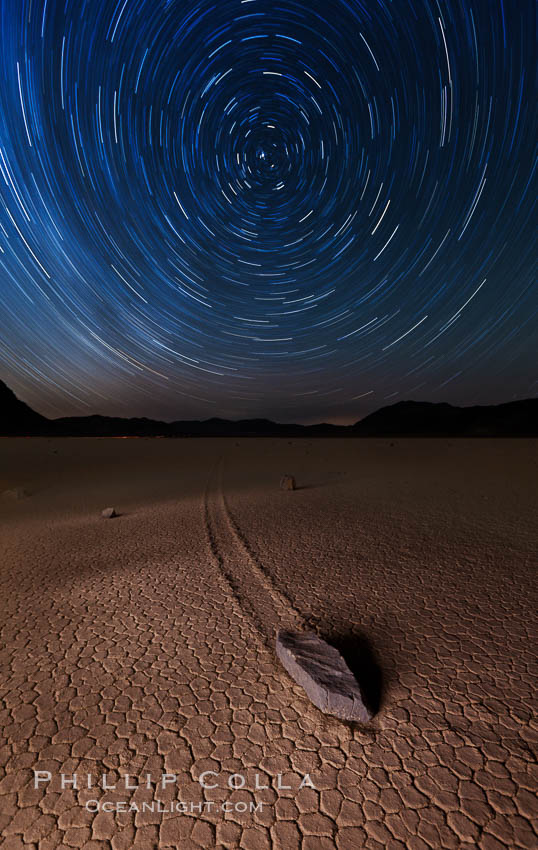 Racetrack sailing stone and star trails.  A sliding rock of the Racetrack Playa. The sliding rocks, or sailing stones, move across the mud flats of the Racetrack Playa, leaving trails behind in the mud. The explanation for their movement is not known with certainty, but many believe wind pushes the rocks over wet and perhaps icy mud in winter. Racetrack Playa, Death Valley National Park, California, USA, natural history stock photograph, photo id 27667