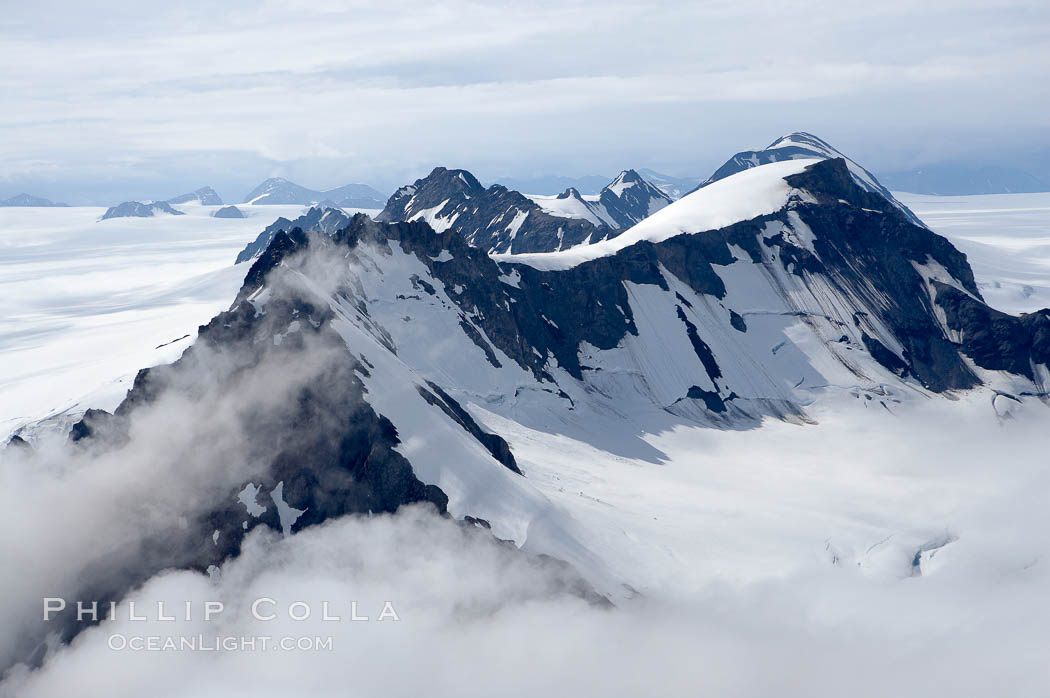 The Kenai Mountains rise above thick ice sheets and the Harding Icefield which is one of the largest icefields in Alaska and gives rise to over 30 glaciers, Kenai Fjords National Park