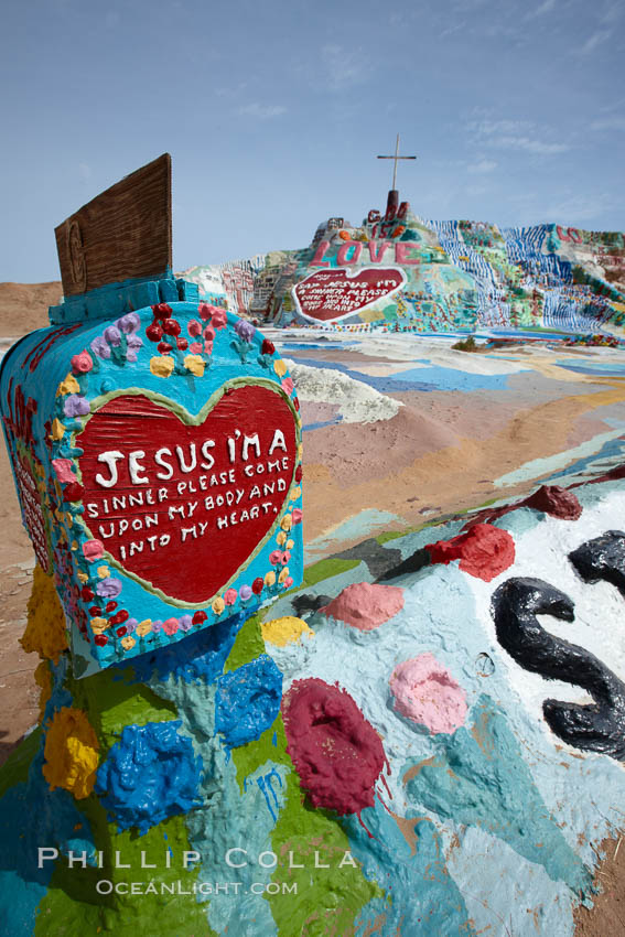 Salvation Mountain, near the desert community of Slab City and the small town of Niland on the east side of the Salton Sea.  Built over several decades by full-time resident Leonard Knight, who lives at the site, Salvation Mountain was built from over 100,000 gallons of paint, haybales, wood and metal and was created by Mr. Knight to convey the message that God Loves Everyone.,  Copyright Phillip Colla, image #22514, all rights reserved worldwide.