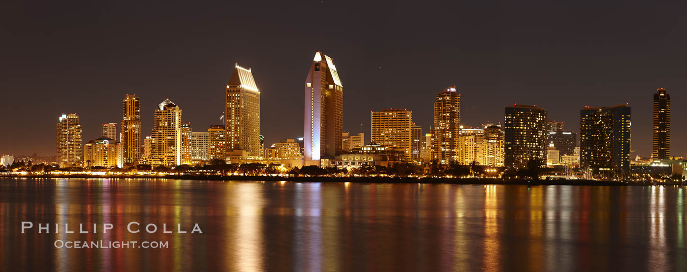 San Diego city skyline at night, showing the buildings of downtown San Diego reflected in the still waters of San Diego Harbor, viewed from Coronado Island.  A panoramic photograph, composite of seven separate images