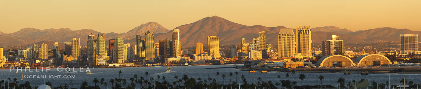San Diego city skyline, showing the buildings of downtown San Diego rising above San Diego Harbor, viewed from Point Loma at sunset, with mountains of the Cleveland National Forest rising in the distance.  A panoramic photograph, composite of six separate images