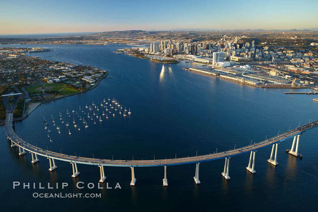 San Diego Coronado Bridge, known locally as the Coronado Bridge, links San Diego with Coronado, California.  The bridge was completed in 1969 and was a toll bridge until 2002.  It is 2.1 miles long and reaches a height of 200 feet above San Diego Bay.  Coronado Island is to the left, and downtown San Diego is to the right in this view looking north, Keywords: aerial, aerial photo, california, coronado bay bridge, coronado bridge, san diego, san diego coronado bridge, usa, city, downtown, scene, urban, view, vista, bay, bridge, harbor, marine, ocean, sea, span, transportation, water, coronado, freeway, road, landmark, scenic, structure, travel, marina, outdoors, outside, tourism, island, above, over,  Copyright Phillip Colla, image #22288, all rights reserved worldwide.