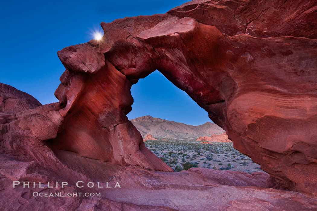 Natural arch formed in sandstone frames the setting moon, Valley of Fire State Park