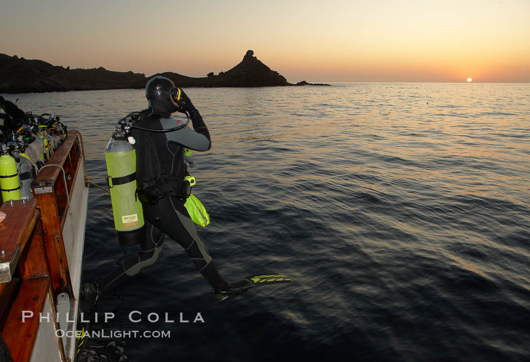 A SCUBA diver leaps into the water, from boat Horizon, into the kelp forest and rich waters of San Clemente Island, China Hat Point, Balanced Rock, sunrise