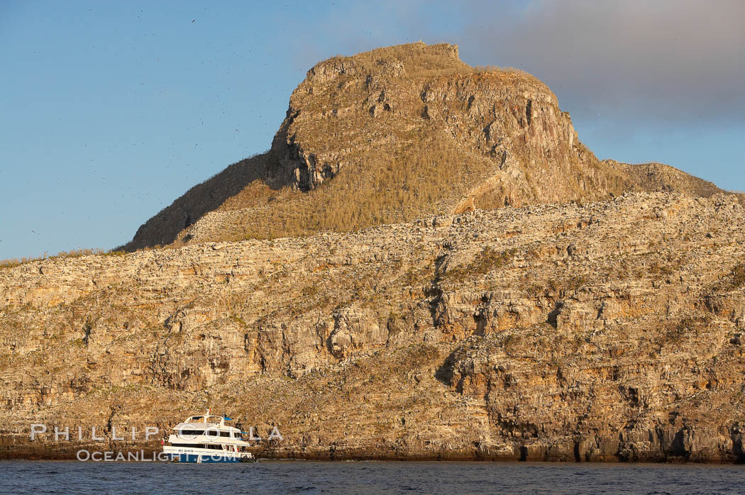Wolf Island, with a liveaboard tour boat below sheer seacliffs, is the largest of the islands in the distant northern island group of the Galapagos archipelago, is home to hundreds of thousands of seabirds.  Vast schools of sharks and fish inhabit the waters surrounding Wolf Island