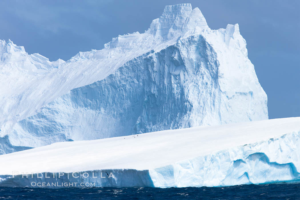 Two icebergs, South Orkney Islands.  The foreground berg is a tabular iceberg, canted with a slight angle, showing the characteristic flat top and sheer sides.