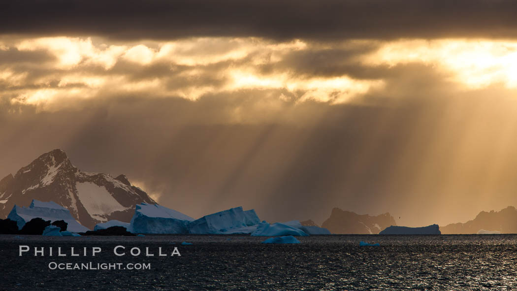 Dawn in the South Orkney Islands. Sunlight breaks through clouds to light up icebergs and the moutainous southern coast of Coronation Island