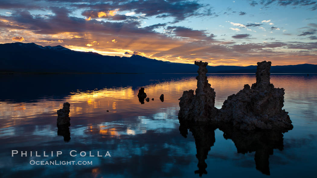Tufa towers rise from Mono Lake, with the Eastern Sierra visible in the distance. Tufa towers are formed when underwater springs rich in calcium mix with lakewater rich in carbonates, forming calcium carbonate (limestone) structures below the surface of the lake. The towers were eventually revealed when the water level in the lake was lowered starting in 1941. Mono Lake, California, USA, natural history stock photograph, photo id 26983