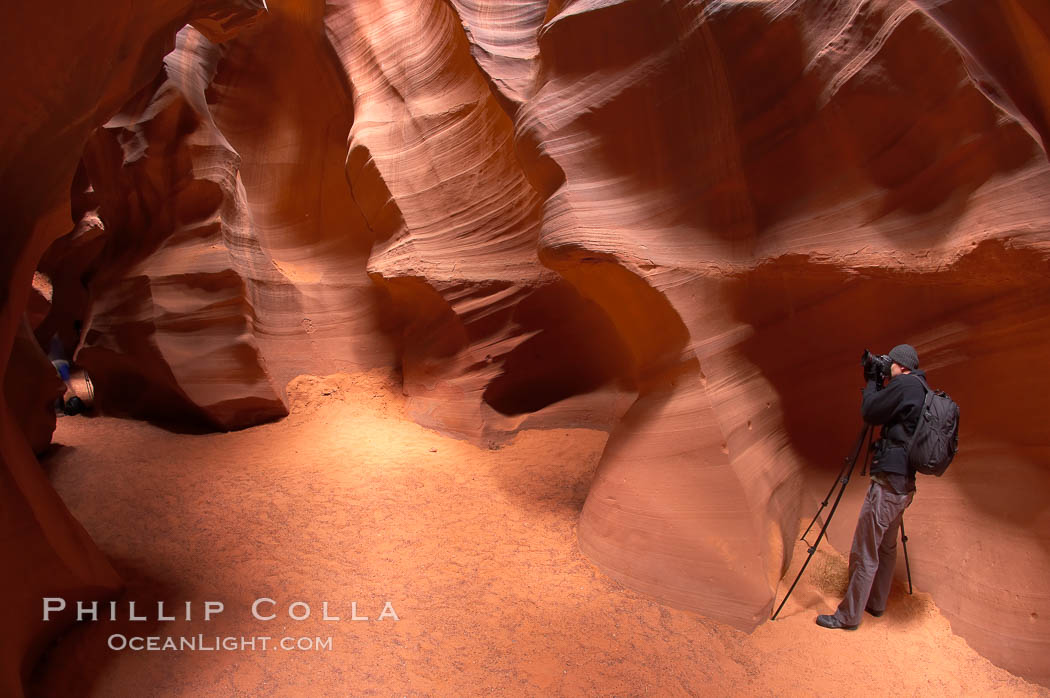 A photographer works amidst the striated walls and dramatic light within Antelope Canyon, a deep narrow slot canyon formed by water and wind erosion, Navajo Tribal Lands, Page, Arizona