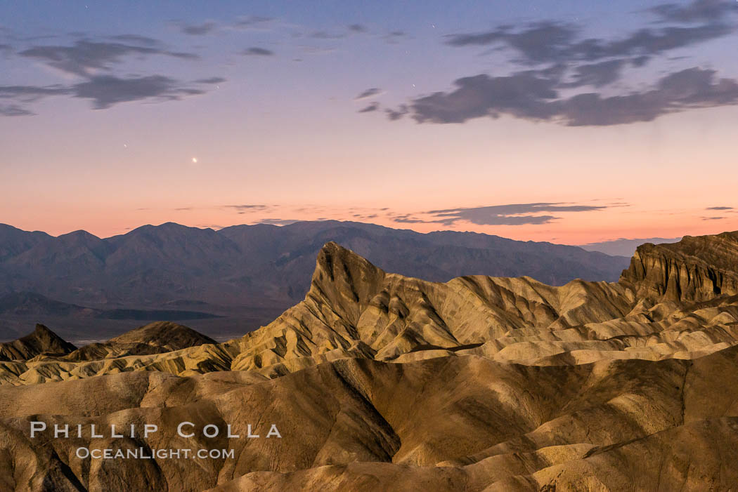 Venus sets over Manley Beacon and the Panamint Mountains, viewed from Zabriskie Point, landscape lit by a full moon, evening, stars, Death Valley National Park, California