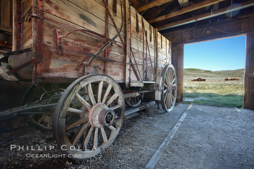 Wagon and interior of County Barn, Brown House and Moyle House in distance, Bodie State Historical Park, California
