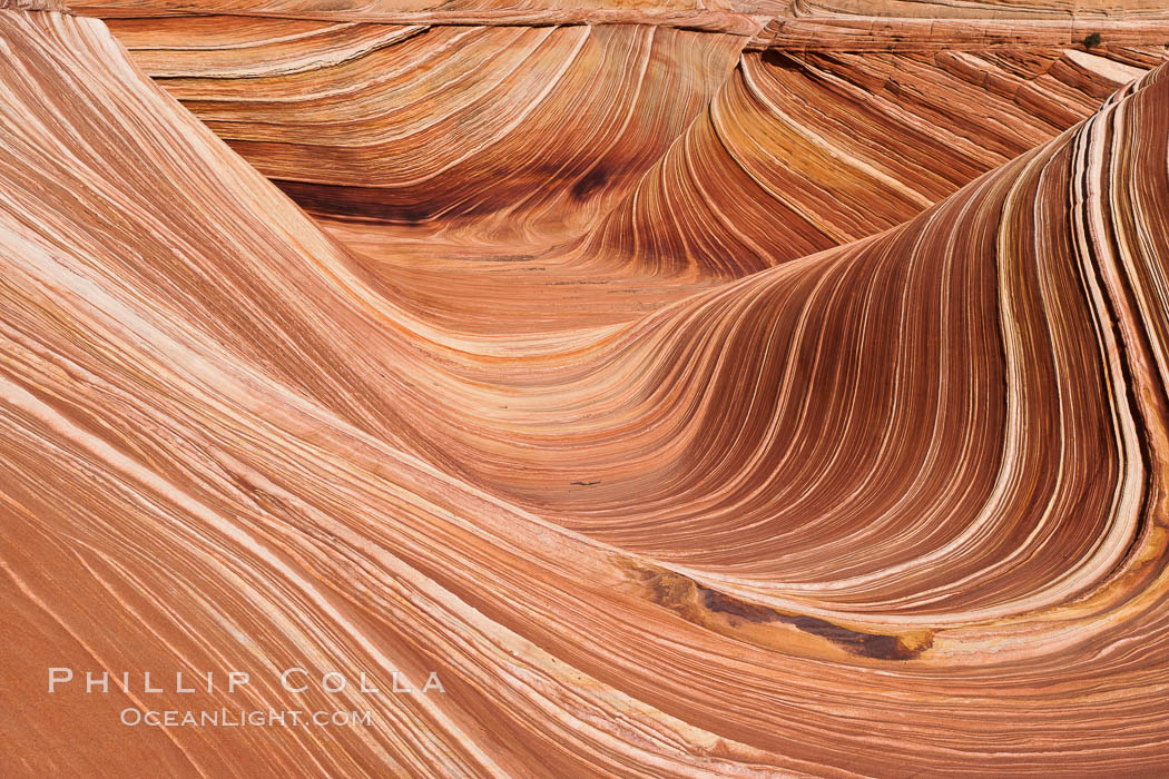 The Wave, an area of fantastic eroded sandstone featuring beautiful swirls, wild colors, countless striations, and bizarre shapes set amidst the dramatic surrounding North Coyote Buttes of Arizona and Utah.  The sandstone formations of the North Coyote Buttes, including the Wave, date from the Jurassic period. Managed by the Bureau of Land Management, the Wave is located in the Paria Canyon-Vermilion Cliffs Wilderness and is accessible on foot by permit only.,  Copyright Phillip Colla, image #20614, all rights reserved worldwide.