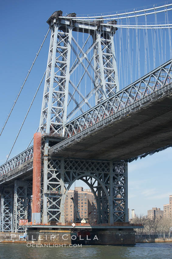 The Williamsburg Bridge viewed from the East River.  The Williamsburg Bridge is a suspension bridge in New York City across the East River connecting the Lower East Side of Manhattan at Delancey Street with the Williamsburg neighborhood of Brooklyn on Long Island at Broadway near the Brooklyn-Queens Expressway.,  Copyright Phillip Colla, image #11124, all rights reserved worldwide.