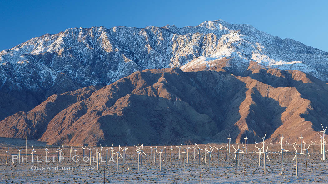 Wind turbines, rise above the flat floor of the San Gorgonio Pass near Palm Springs, with snow covered Mount San Jacinto in the background, provide electricity to Palm Springs and the Coachella Valley.,  Copyright Phil Colla, image #22209, all rights reserved worldwide.