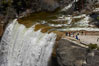 Vernal Falls at peak flow in late spring. Hikers are seen at the precipice to Vernal Falls, having hiked up the Mist Trail to get there. Vernal Falls, Yosemite National Park, California, USA