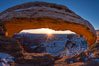 Mesa Arch spans 90 feet and stands at the edge of a mesa precipice thousands of feet above the Colorado River gorge. For a few moments at sunrise the underside of the arch glows dramatically red and orange. Island in the Sky, Canyonlands National Park, Utah, USA
