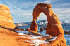 Delicate Arch, dusted with snow, at sunset, with the snow-covered La Sal mountains in the distance.  Delicate Arch stands 45 feet high, with a span of 33 feet, atop of bowl of slickrock sandstone. Delicate Arch, Arches National Park, Utah, USA