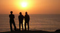 Surf check.  Three guys check the surf from atop a bluff overlooking the waves at the end of the day, at sunset, north of South Carlsbad State Beach. California, USA. Image #19808