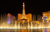 The Bellagio Hotel fountains light up the reflection pool as the half-scale replica of the Eiffel Tower at the Paris Hotel in Las Vegas rises above them, at night. Las Vegas, Nevada, USA. Image #20559
