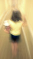 Girl walks down hotel corridor at night, carrying ice bucket, abstract blur time exposure. Image #20571