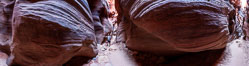 Buckskin Gulch hiker.  A hiker moves through the deep narrow passages of Buckskin Gulch, a slot canyon cut deep into sandstone by years of river-induced erosion.  In some places the Buckskin Gulch narrows are only about 15 feet wide but several hundred feet high, blocking sunlight.  Flash floods are dangerous as there is no escape once into the Buckskin Gulch slot canyons.  This is a panorama made of sixteen individual photos. Paria Canyon-Vermilion Cliffs Wilderness, Arizona, USA. Image #20699