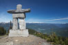 Ilanaaq, the logo of the 2010 Winter Olympics in Vancouver, is formed of stone in the Inukshuk-style of traditional Inuit sculpture.  Located near the Whistler mountain gondola station, overlooking Whistler Village and Green Lake in the distance. British Columbia, Canada. Image #21009