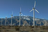 Wind turbines, rise above the flat floor of the San Gorgonio Pass near Palm Springs, with snow covered Mount San Jacinto in the background, provide electricity to Palm Springs and the Coachella Valley. California, USA. Image #22208