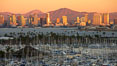 San Diego city skyline, showing the buildings of downtown San Diego rising above San Diego Harbor, viewed from Point Loma with the San Diego Yacht Club in the foreground, sunset. San Diego, California, USA. Image #22248