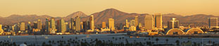 San Diego city skyline, showing the buildings of downtown San Diego rising above San Diego Harbor, viewed from Point Loma at sunset, with mountains of the Cleveland National Forest rising in the distance.  A panoramic photograph, composite of six separate images. San Diego, California, USA