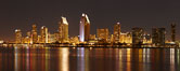 San Diego city skyline at night, showing the buildings of downtown San Diego reflected in the still waters of San Diego Harbor, viewed from Coronado Island.  A panoramic photograph, composite of seven separate images. San Diego, California, USA. Image #22254