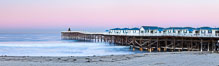 The Crystal Pier and Pacific Ocean at sunrise, dawn, waves blur as they crash upon the sand.  Crystal Pier, 872 feet long and built in 1925, extends out into the Pacific Ocean from the town of Pacific Beach. California, USA