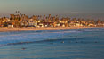 The coast of Oceanside California, waves and surfers, beach houses, just before sunset, winter, looking south. Oceanside Pier, USA. Image #27606