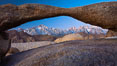 Mount Whitney and Lone Pine Peak are framed by Lathe Arch in the Alabama Hills at sunrise, California. Alabama Hills Recreational Area, USA. Image #27624
