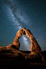 Milky Way arches over Delicate Arch, as stars cover the night sky. Arches National Park, Utah, USA