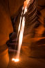 Light Beam in Upper Antelope Slot Canyon.  Thin shafts of light briefly penetrate the convoluted narrows of Upper Antelope Slot Canyon, sending piercing beams through the sandstone maze to the sand floor below. Navajo Tribal Lands, Page, Arizona, USA. Image #28573
