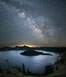 Milky Way and stars over Crater Lake at night. Panorama of Crater Lake and Wizard Island at night, Crater Lake National Park. Oregon, USA. Image #28643