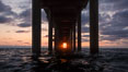 Scripps Pier solstice, surfer's view from among the waves, sunset aligned perfectly with the pier. Research pier at Scripps Institution of Oceanography SIO, sunset. La Jolla, California, USA