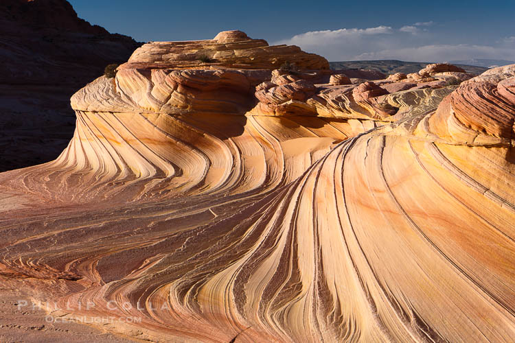 The Second Wave at sunset.  The Second Wave, a curiously-shaped sandstone swirl, takes on rich warm tones and dramatic shadowed textures at sunset.  Set in the North Coyote Buttes of Arizona and Utah, the Second Wave is characterized by striations revealing layers of sedimentary deposits, a visible historical record depicting eons of submarine geology.