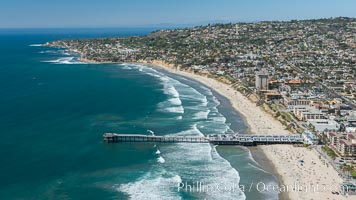 Aerial Photo of Crystal Pier, 872 feet long and built in 1925, extends out into the Pacific Ocean from the town of Pacific Beach. Mission Bay and downtown San Diego are seen in the distance