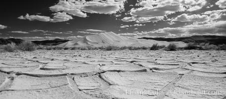 Arid and barren mud flats, dried mud, with the tall Eureka Dunes in the distance, Eureka Valley, Death Valley National Park, California