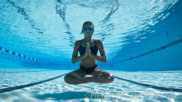 Athletic young girl with perfect buoyancy control underwater, performing isometric exercises while breathholding