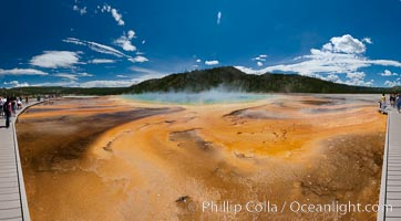 Bacteria mats and Grand Prismatic Spring.  The orange color is due to bacteria which thrive only on the cooler fringes of the hot spring, while the hotter center of the spring hosts blue-colored bacteria, Midway Geyser Basin, Yellowstone National Park, Wyoming
