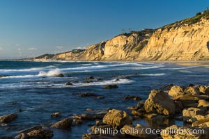 Black's Beach sea cliffs, sunset, looking north from Scripps Pier with Torrey Pines State Reserve in the distance, La Jolla, California